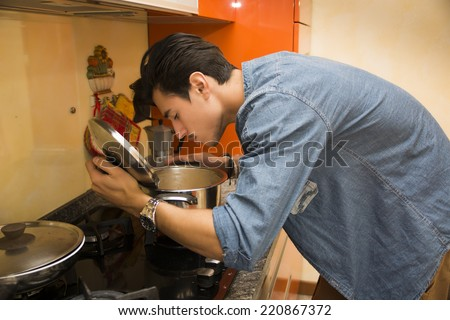 Young man smelling the food in the pot as he cooks his evening meal in a modern kitchen with orange decor - stock photo