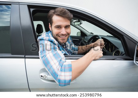 Young man smiling and driving in his car - stock photo