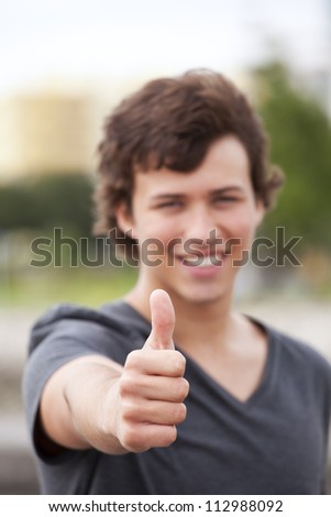 young man smiling and gesturing OK (selective focus on the hand) - stock photo