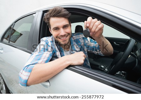 Young man smiling and holding key in his car - stock photo