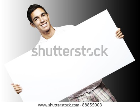 young man smiling and showing a big banner against a black background - stock photo