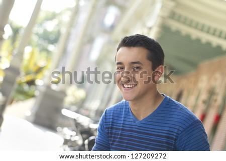 Young man smiling at camera, outdoors - stock photo