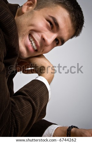 young man smiling, bent on table, studio shot - stock photo