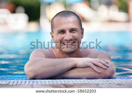 Young man smiling happy to the edge of a pool with clear blue water