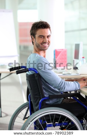 Young man smiling in wheelchair - stock photo