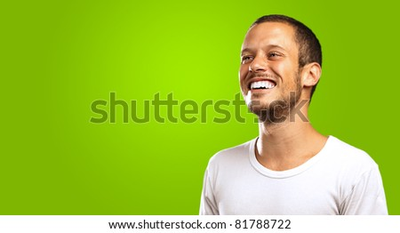young man smiling on a green background - stock photo