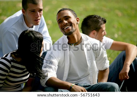 Young man smiling sitting in the grass - stock photo