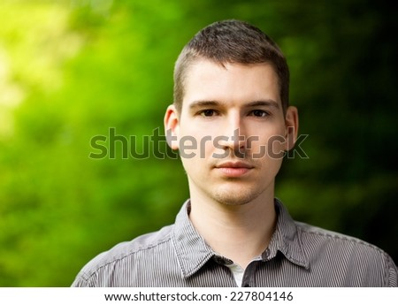 Young man smiling. Vibrant green leaves as a background. - stock photo