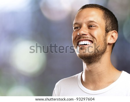 young man smiling with a blurred city as a background - stock photo