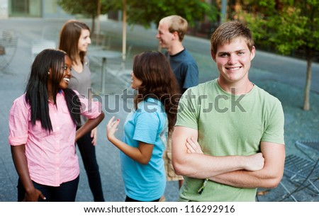 Young man smiling with friends in the background - stock photo