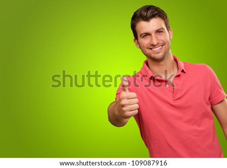 young man smiling with thumbs up isolated on a green background - stock photo