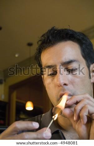 Young man smoking a cigar - stock photo