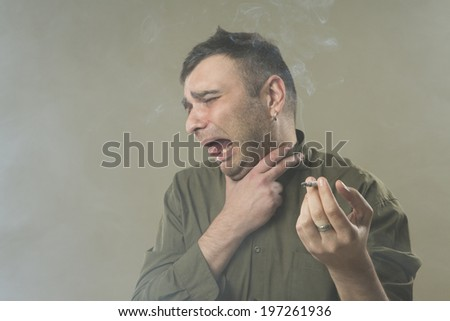 Young man smoking a cigarette badly. Suffocating. Quit and give up smoking. . smoking kills. Space in the cigarette smoke. Gray background. Studio shot. - stock photo