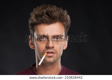 Young man smoking cigarette on black background. Handsome young man with brown hair wearing red t-shirt