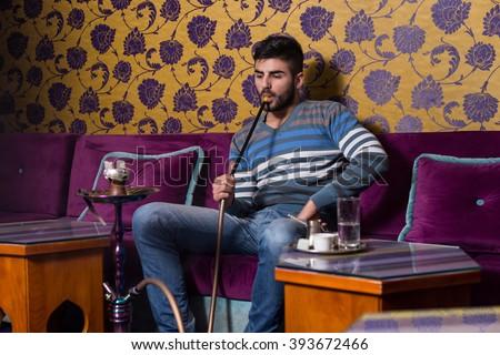 Young Man Smoking Shisha At Arabic Restaurant - Man Exhaling Smoke Inhaling From A Hookah - stock photo