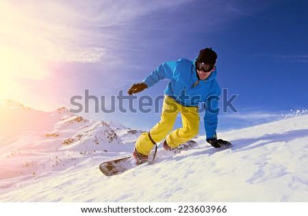 Young man snowboarding. - stock photo