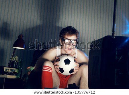 Young man soccer fanatic watching soccer match in television - stock photo