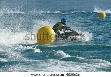 Young man speeding on jet ski - stock photo