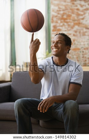 Young man spinning basketball on finger - stock photo