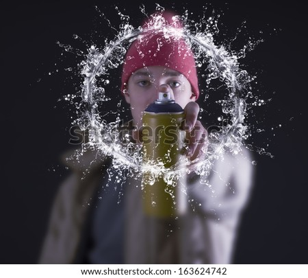 Young man spraying paint at the concrete wall - stock photo