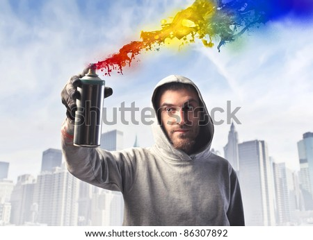Young man spraying some colored paint with cityscape in the background - stock photo