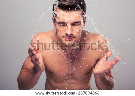 Young man spraying water on his face over gray background - stock photo