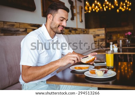 Young man spreading butter on a toast at the cafe - stock photo