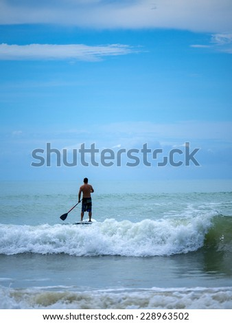 Young man stand up paddle boarding in Thailand on a stormy day - stock photo