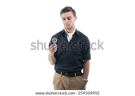 Young man standing against the wall alone with bulb in his nads. Concept: generating ideas - stock photo