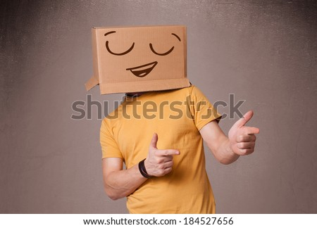 Young man standing and gesturing with a cardboard box on his head with smiley face
