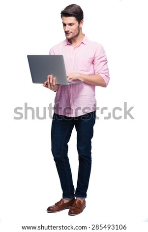 Young man standing and using laptop isolated on a white background - stock photo