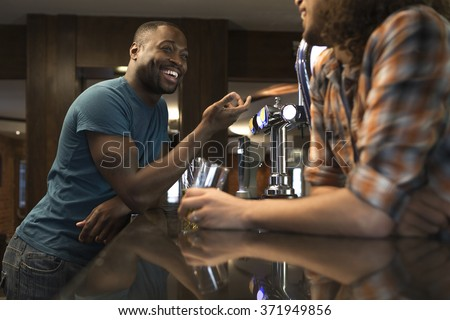 Young man standing at the bar talking to the bartender - stock photo