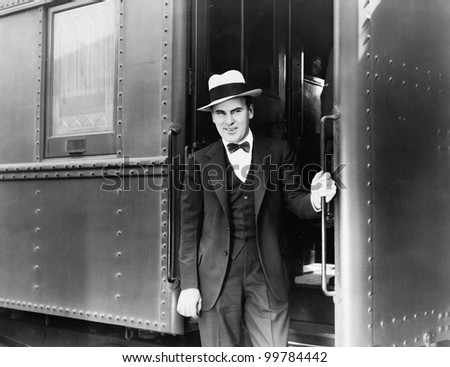 Young man standing at the entrance of a train - stock photo