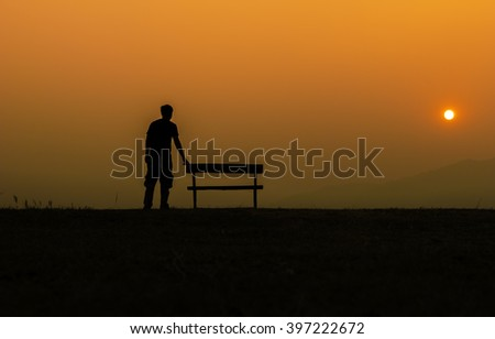 young man standing ba a chair watching an sunset silhouetted - stock photo