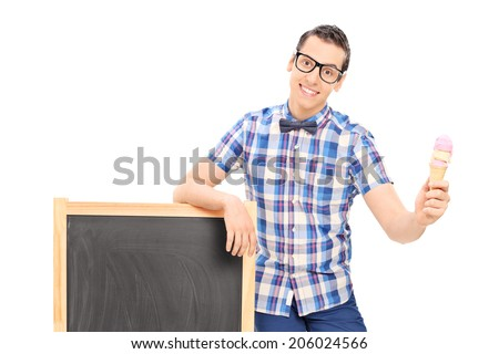 Young man standing by a blackboard and holding an ice cream isolated on white background - stock photo