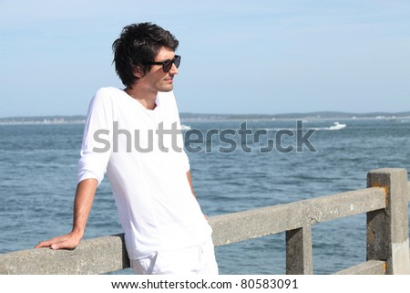 Young man standing by the sea - stock photo