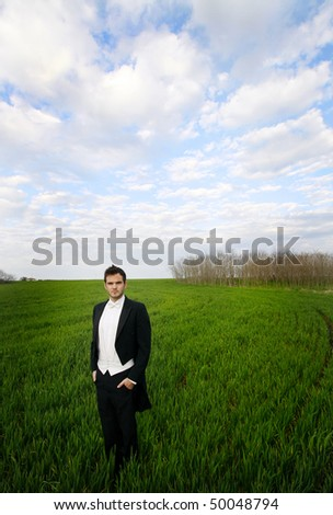 Young man standing in a field, wearing a tuxedo. - stock photo