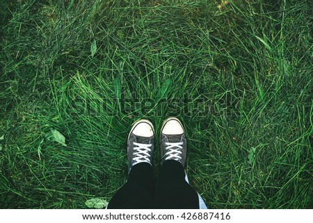 Young man standing in freshly mown grass lawn, top view of casually dressed person in sneakers - stock photo