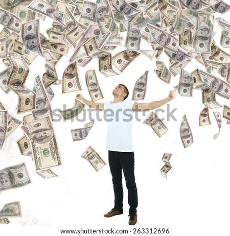 Young man standing in rain of money - stock photo