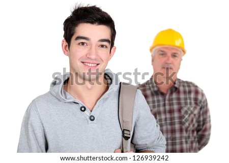 Young man standing next to an experienced worker - stock photo