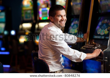 young man standing next to the slot machine smiling - stock photo