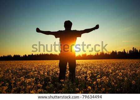 Young man standing on a meadow with dandelions on sunset sky background