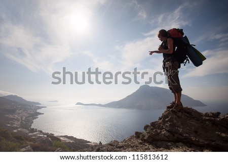 Young man standing on a rock against picturesque view of sea - stock photo