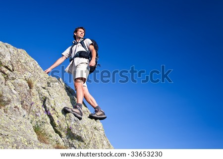 Young man standing on a rock over a deep blue sky background. Large copy-space on the right. Low angle view