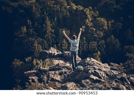 young man standing on a rock slope - stock photo