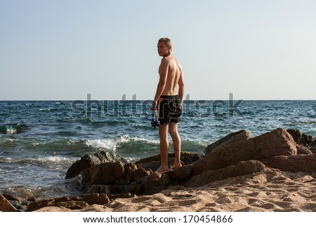 Young man standing on a stone at sunny beach