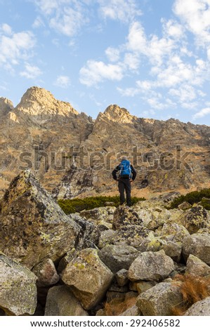 Young man standing on boulders in front of a mountain top with blue backpack  - stock photo