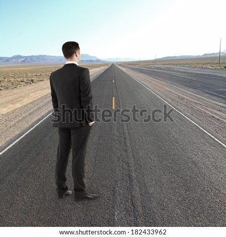 young man standing on road looking to horizont