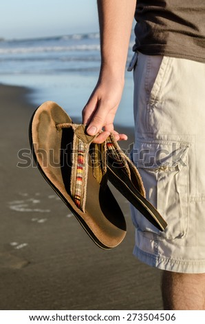 Young man standing on the beach with slippers in hand - stock photo