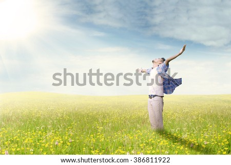 Young man standing on the meadow while enjoying his happy time and raise hands, shot in the springtime